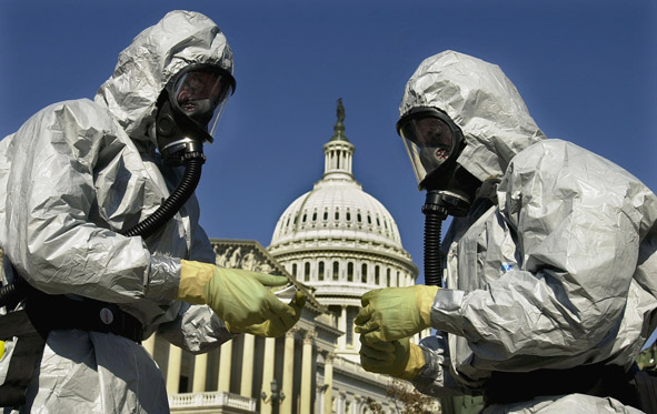 People in biohazard suits in front of the Capitol