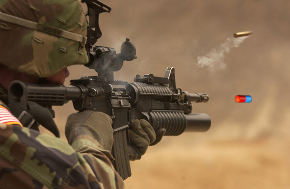 Solider firing rifle with a pill emerging from barrel