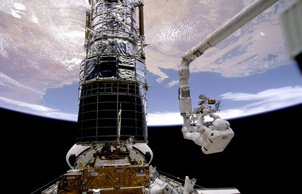 Astronaut outside shuttle working on Hubble telescope with Earth in the background