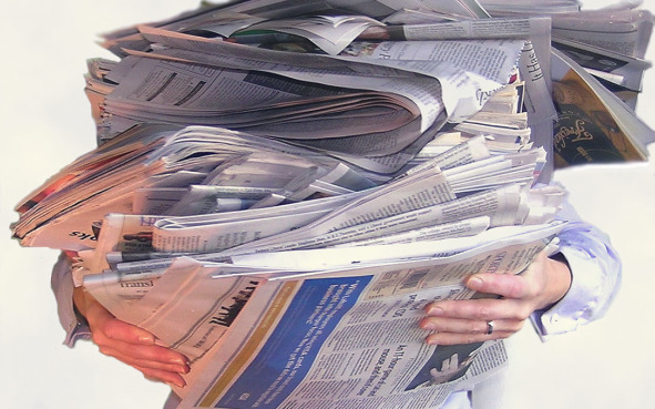 person holding stack of newspapers
