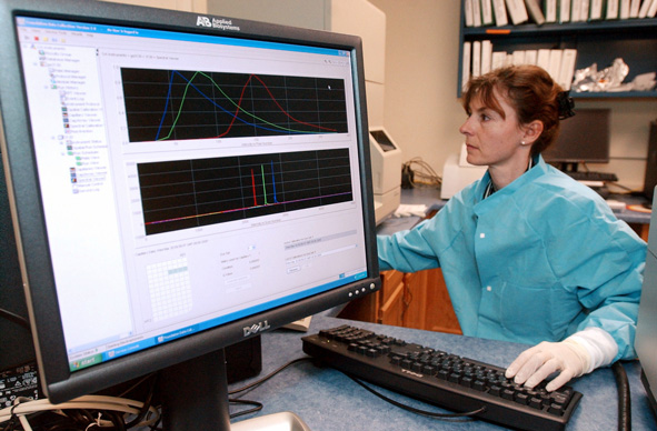 a forensic scientist runs a DNA sample on a computer at the Vermont Forensic