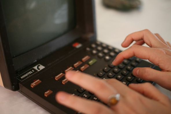 close up of hands tying on a dark Minitel terminal