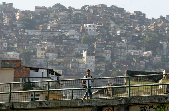 A student crosses a bridge to arrive to his school, on the background is seen the Rocinha slum in Rio de Janeiro, Brazil