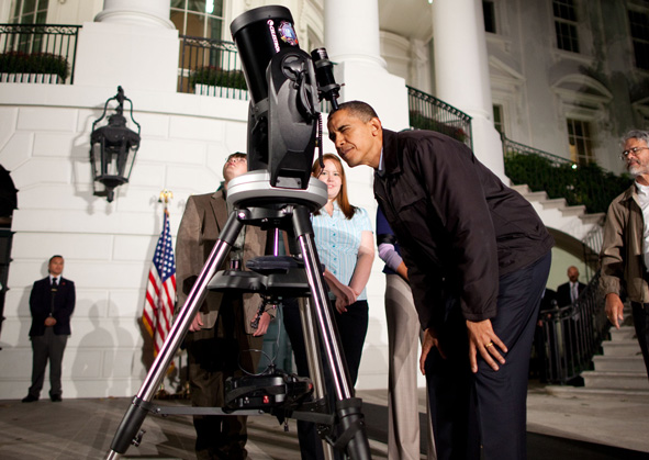 President Obama peers into a telescope during the Astronomy Night event on the South Lawn of the White House