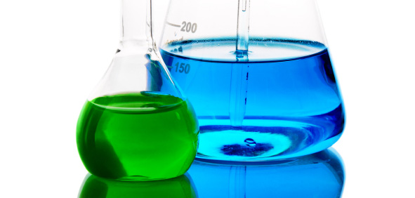 two scientific beakers, one with green liquid, another with blue liquid